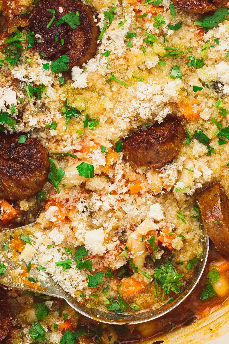 vegan sausage casserole with ladle zoomed