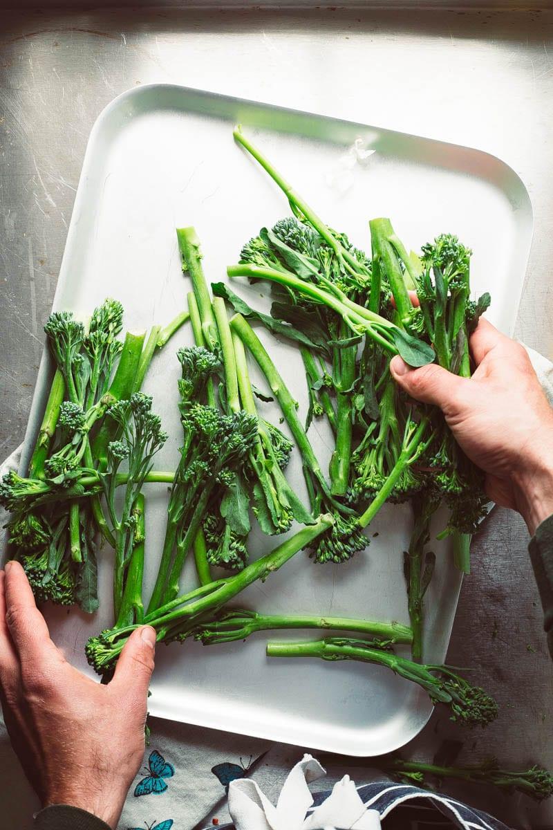 holding tenderstem broccoli over tray
