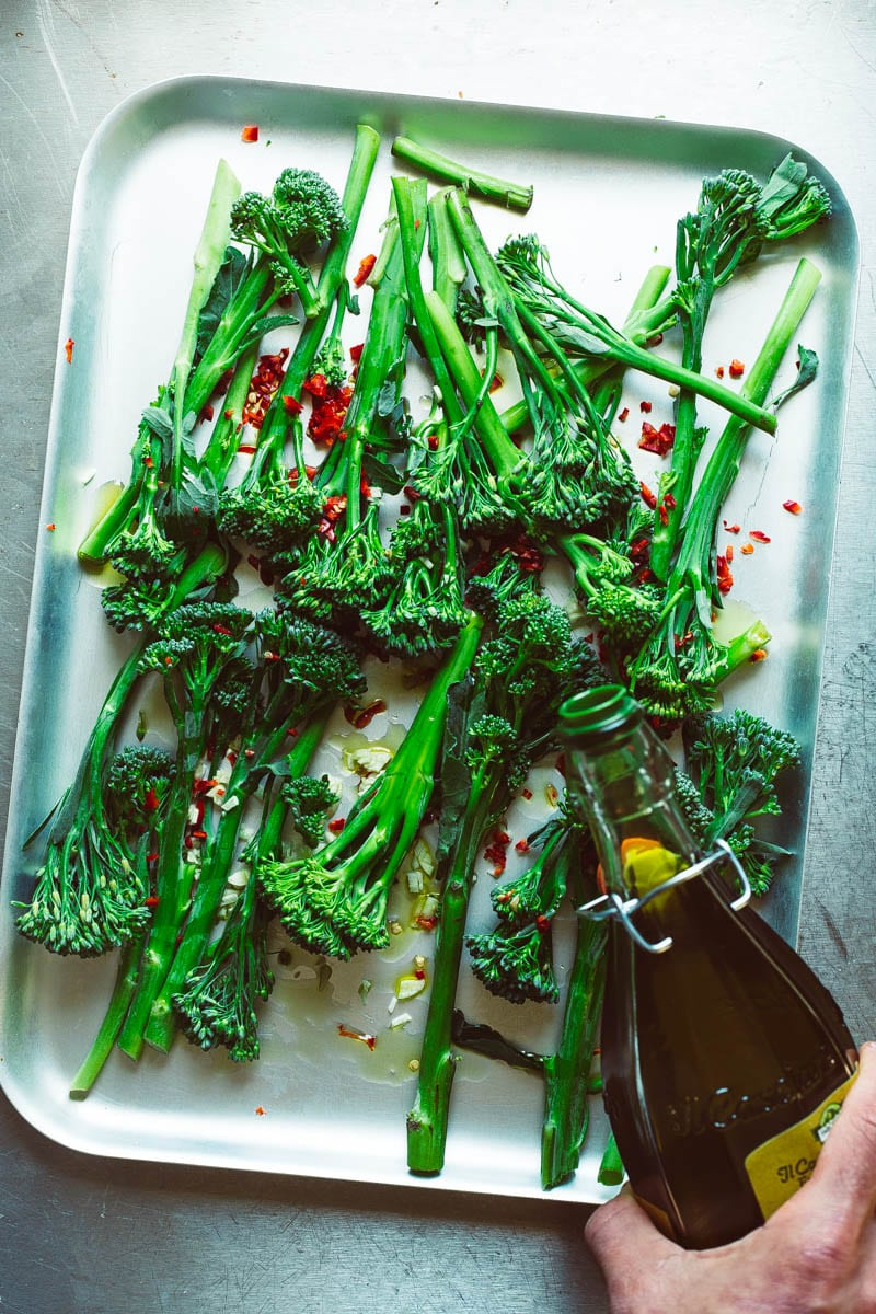pouring olive oil over tenderstem broccoli
