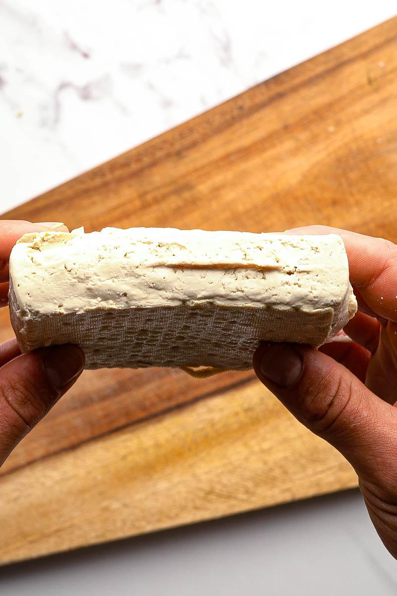 pressed tofu between hands
