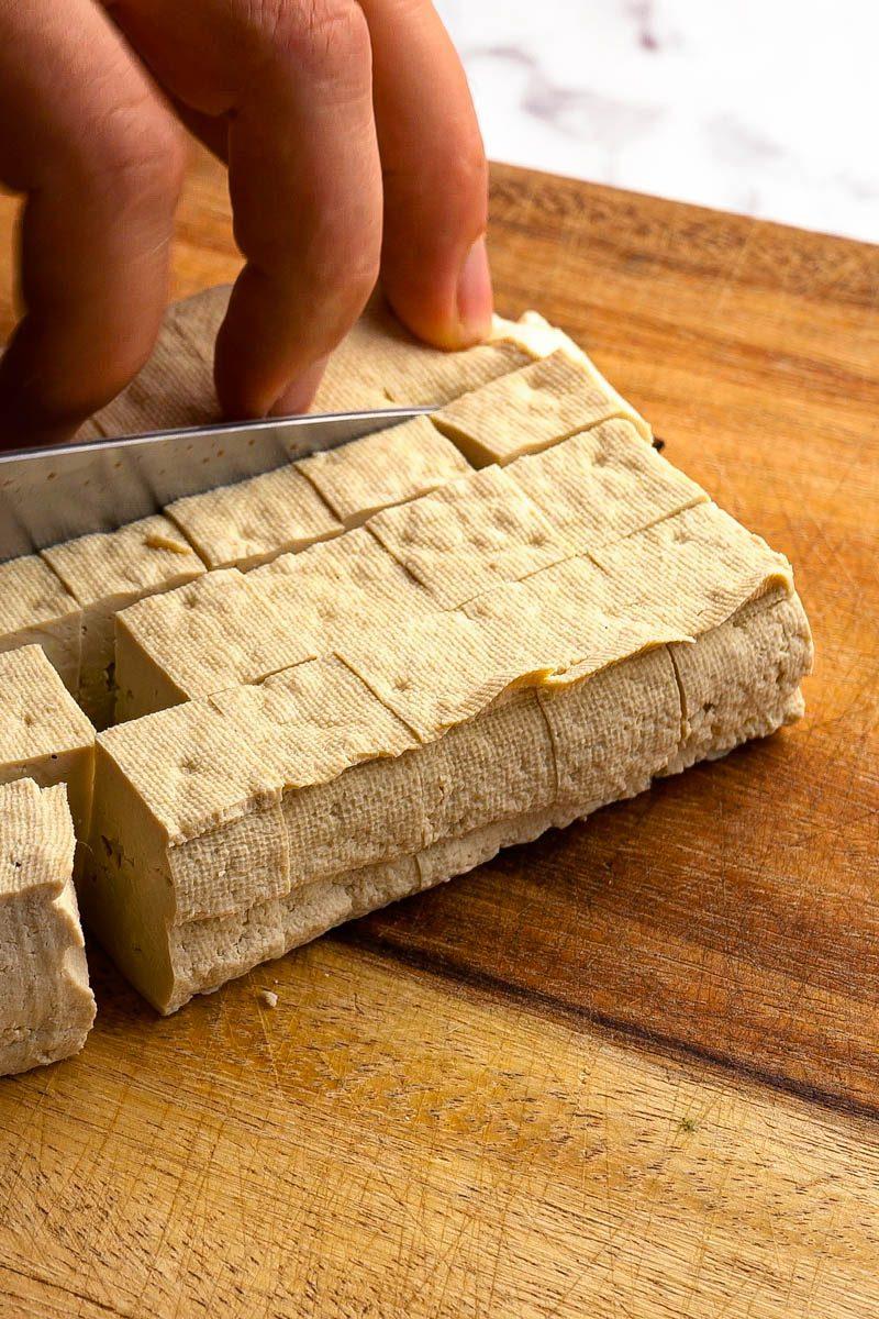 chopping tofu into cubes
