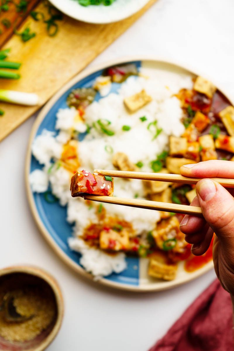 holding baked tofu piece with sauce on