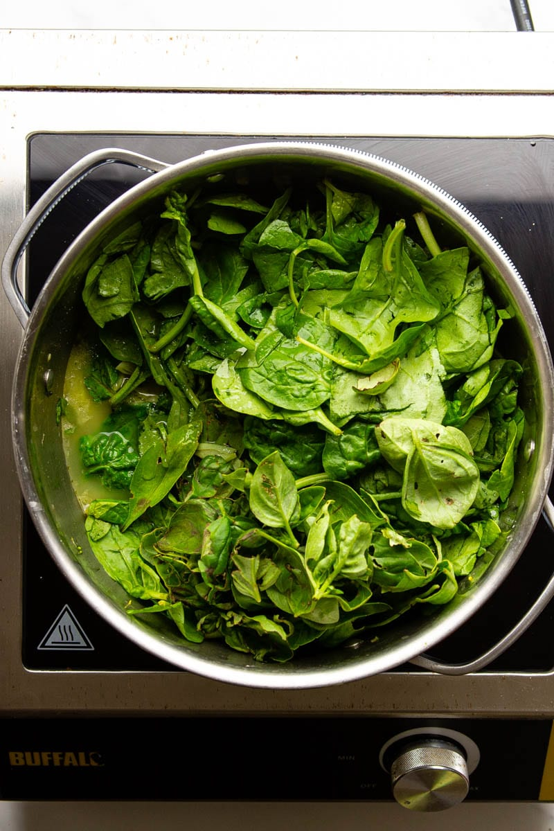 spinach heaped into a pan