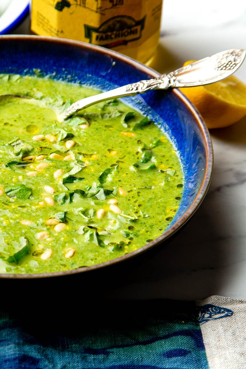 broccoli and spinach soup side on with olive oil in background