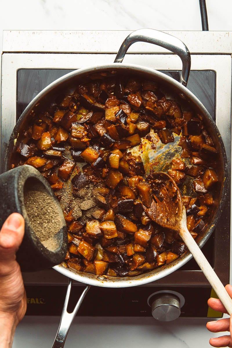stirring in black pepper to aubergines