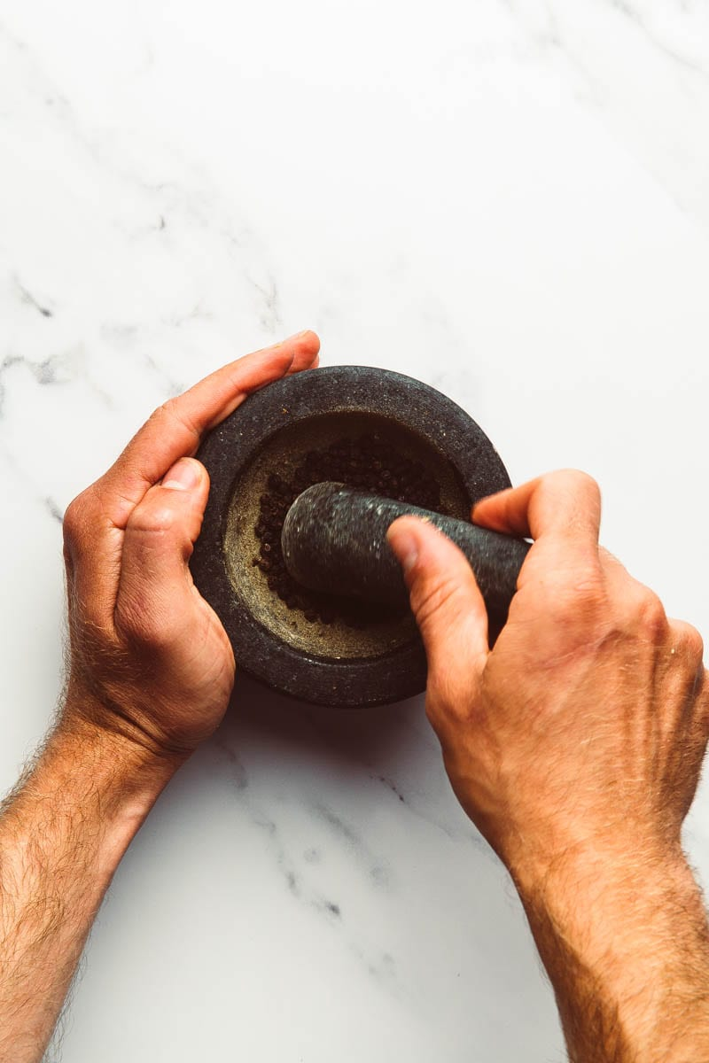 breaking pepper with pestle and mortar