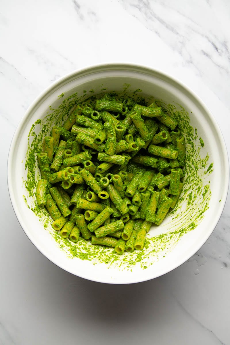 pasta with pesto in mixing bowl