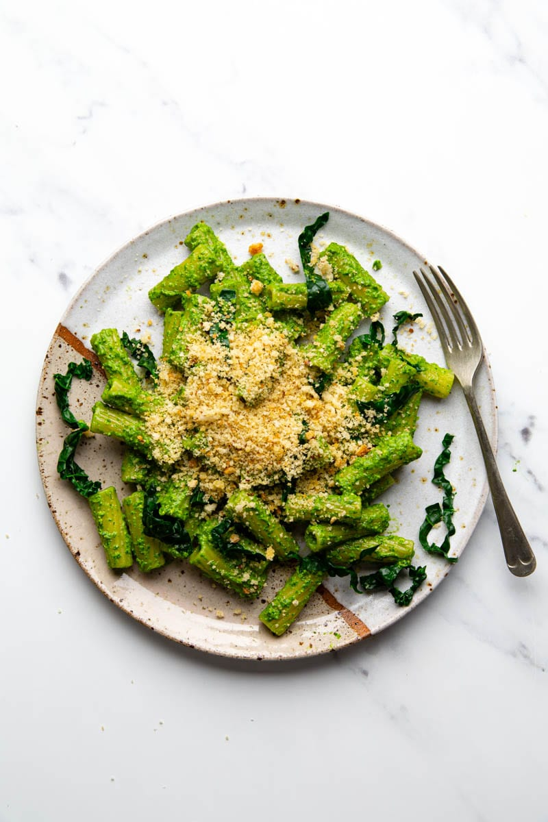 spinach pesto with pasta on plain background